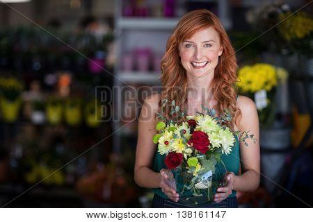 Portrait of female florist holding flower vase at flower shop
