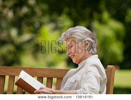 Reired Woman Reading A Book On The  Bench