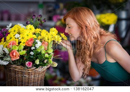 Smiling female florist smelling flowers at flower shop