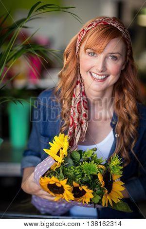 Portrait of smiling female florist holding bunch of flower in flower shop