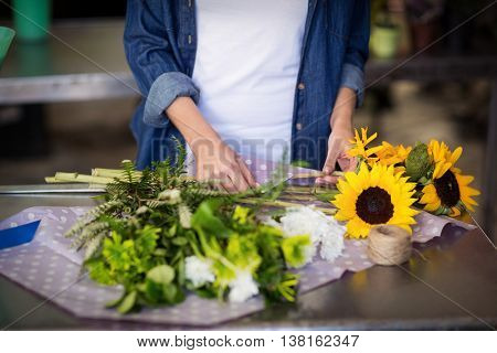 Mid-section of female florist wrapping flower bouquet in flower shop