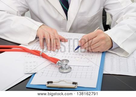 Doctor checking an Ecg paper in his medical studio
