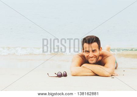 Handsome man lying on the beach by the water