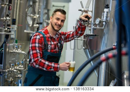 Portrait of happy brewer testing beer at brewery