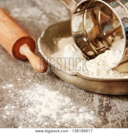 Flour Metal Bowl With Wooden Rolling Pin On Stone Table