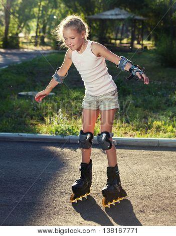 Girl skating outdoors. Child on roller skates
