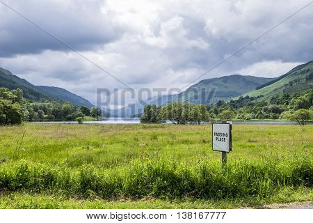 Beautiful Scottish scenery of Passing Place sign in front of Loch Voil near Balquhidder with hills and glens in the distance.