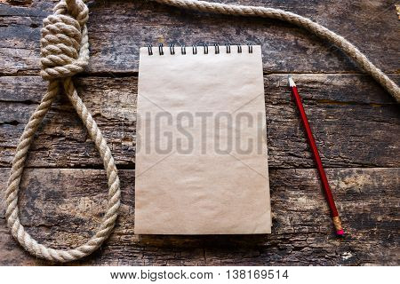 notebook and a loop for suicide on wooden background