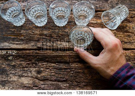 man drinks vodka on wooden background on wooden background