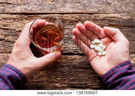 man holding a glass of alcohol and a handful of pills