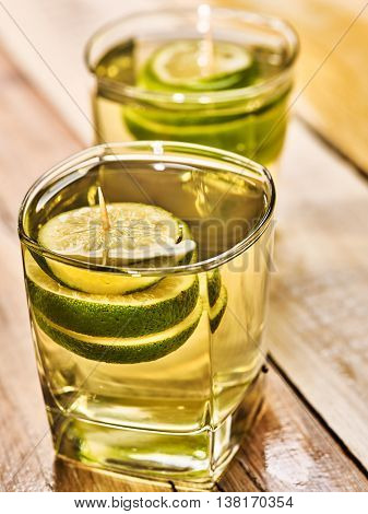 Alcohol drink. On wooden boards are two glasses with alcohol green transparent drink. Drink number hundred and three cocktail green tea with lime. Country life. Light background.