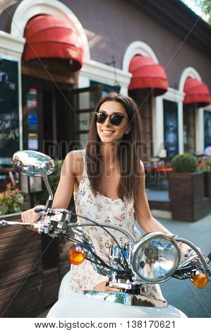 Beauty on scooter. Excited young and beautiful woman waiting on a scooter on the street