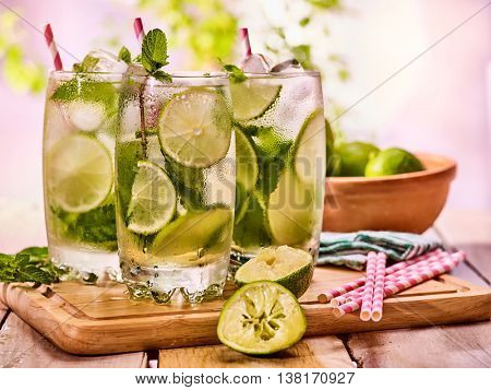 Alcohol drink. On wooden boards three glasses with ice cubes alcohol drink . A drink number hundred fourteen cocktail mohito with straw and lime and mint leaf. Country life. Outdoor. Light background.