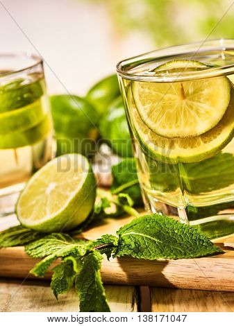 Country drink. On wooden boards are two glasses with green transparent drink . A drink number hundred five mojito with mint leaf on sunlight . Country life. Light background.