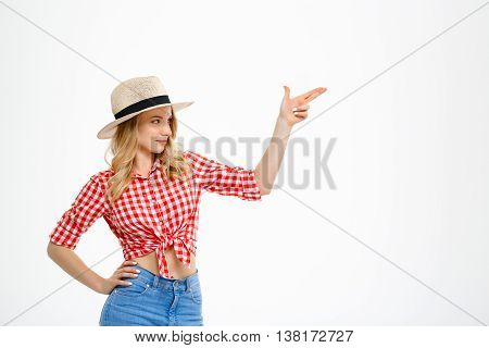 Portrait of young beautiful country girl in hat, jeans and shirt smiling, pointing fingers in side over white background. Copy space.