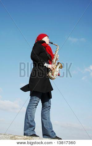 Beautiful girl plays on a saxophon