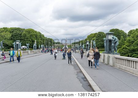 OSLO, NORWAY - JULY 1: Tourists enjoying the beautiful weather visit the Vigeland Sculpture Arrangement in Frogner Park on July 1, 2016 in Oslo, Norway.