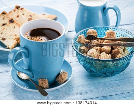 Cup of coffee, milk jug, cane sugar cubes and fruit-cake on old blue wooden table.
