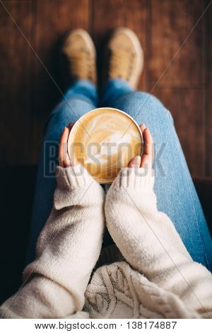 Close up of girl's hands holding a cup of coffee indoors. Top view and feet