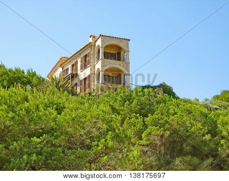 Apartment building / house accommodation view of balconies green trees / bushes in front blue sky