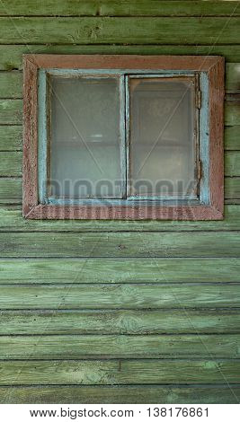 A small old closed window in green rustic wooden wall of an old wooden house