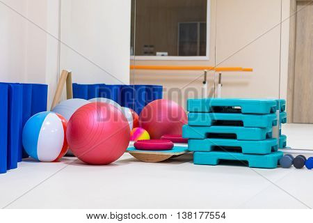 interior of rehabilitation gym with equiment: balls mats steps mirror
