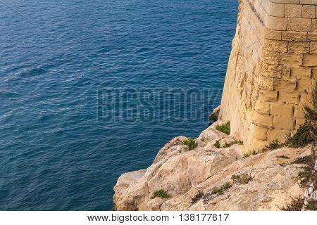 Valletta capital of Malta's defensive sea wall overlooking Marsamxett harbor. With copyspace