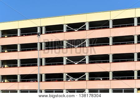Facade of of multistory above ground parking. Concrete frame building with horizontal balconies.
