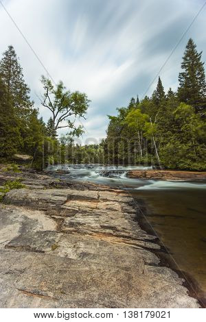 Furnace Falls located in Ontario. Al long exposure to capture the movement of the clouds and trees in the breeze.