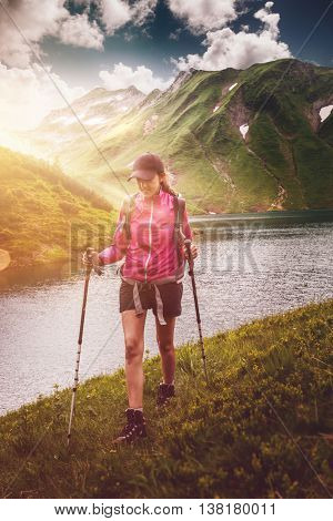 Active fit woman hiking alongside an alpine lake with her backpack and trekking poles approaching the camera with the glow from the sun behind her