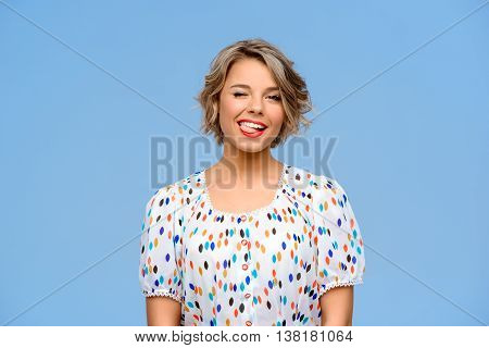 Portrait of young beautiful girl smiling, winking, looking at camera over blue background. Copy space.