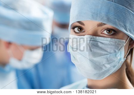 Close-up portrait of young female surgeon doctor surrounded by her team. Group of surgeon in operation theatre. Healthcare medical education emergency medical service and surgery concept