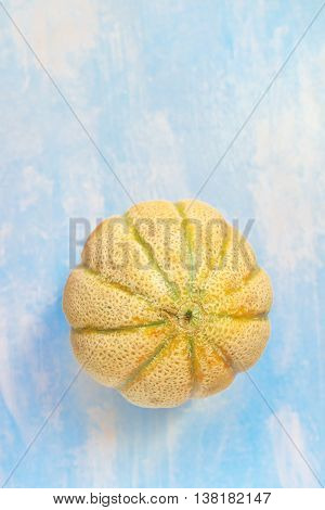 Cantaloupe melon on rustic wooden table top view of whole fruit