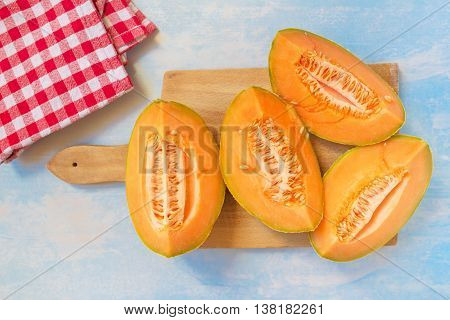 Cantaloupe melon slices on rustic wooden table top view selective focus