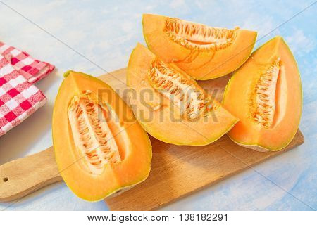 Cantaloupe melon slices on rustic wooden table selective focus