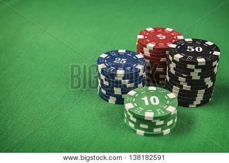 Gambling chips on green card table background