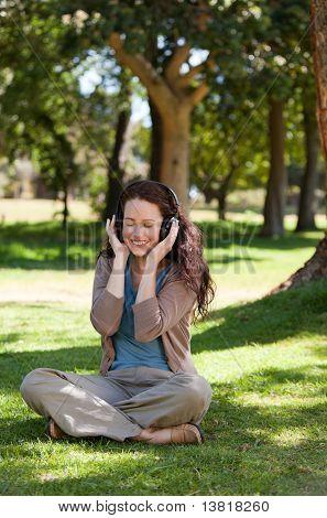 Mulher escuta alguma música no jardim