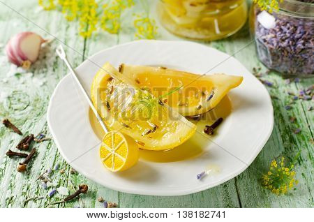 Preserved lemons with salt lavender garlic and cloves on a wooden table and spices on background