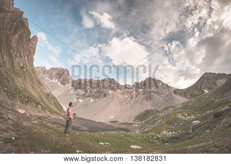 Hiker holding mug and relaxing in alpine valley with lake. Summer adventures and exploration on the Alps. Dramatic sky toned image.