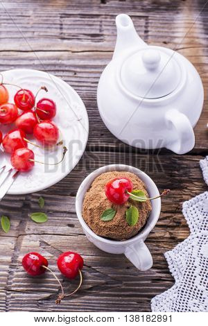 Chocolate cup cake with fresh cherries in ceramic cup on a wooden background served for tea. selective focus