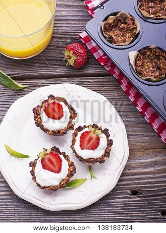 Healthy breakfast. Homemade granola cup with yogurt and fresh Strawberry on a simple wooden background on a ceramic plate. selective focus