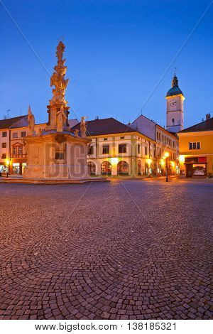 Monument and the town hall tower in a square of the old town of Uherske Hradiste early in the morning.
