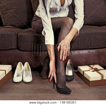 woman trying on several pairs of shoes in the mall