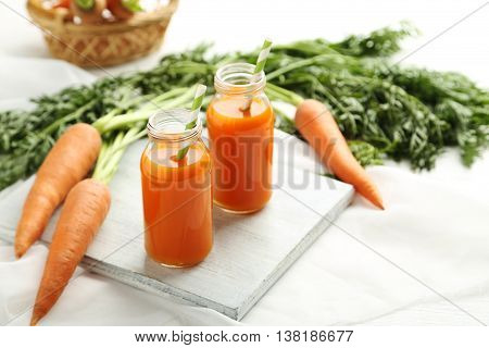 Fresh Carrot Juice In Bottles On A White Wooden Table