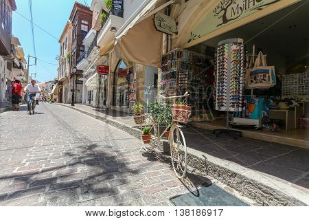 GREECE, ISLAND CRETE, RETHYMNON  - JULY 01, 2016: The tourist shop on the street of the old town of Rethymnon and the bicycle with flowers.