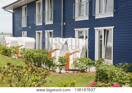 beatiful garden with white beach chairs and blue house