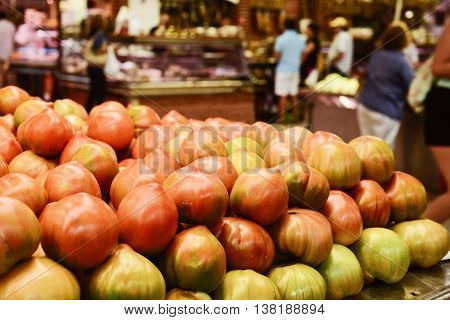 closeup of some tomatoes on sale in a stall in a public market, with unrecognizable buyers in the background