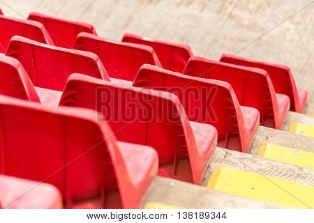 Rows of red stadium seats on concrete stands