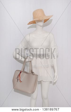 female clothing with hat, bag on mannequin