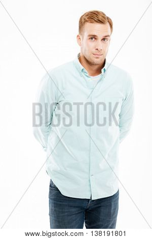 Portrait of serious attractive young man standing with hands behind back over white background